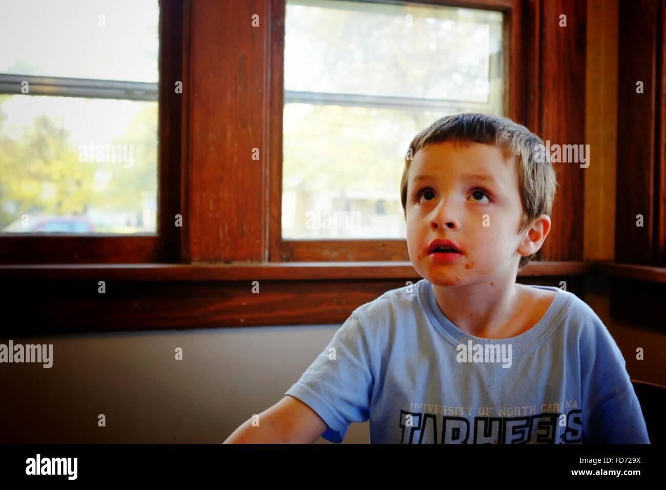 Cute Boy Looking up après le repas à la maison Photo Stock