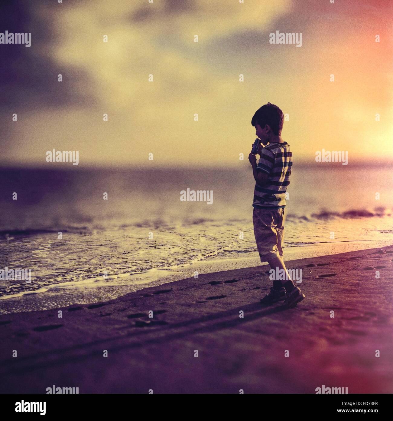Boy Having Ice Cream au Beach pendant le coucher du soleil Photo Stock