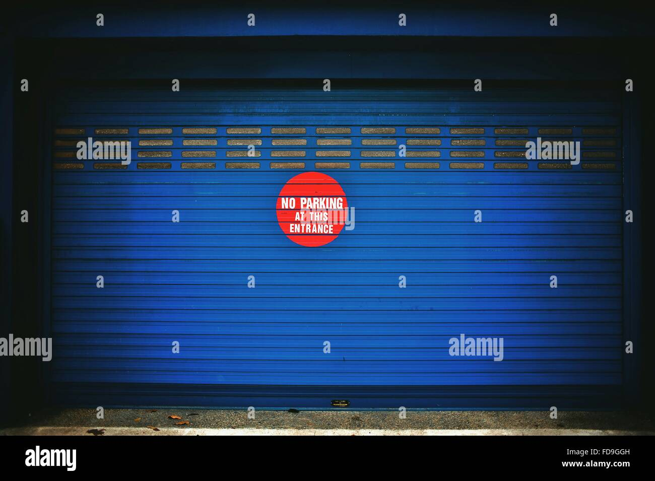 No Parking Sign sur obturateur bleu Photo Stock
