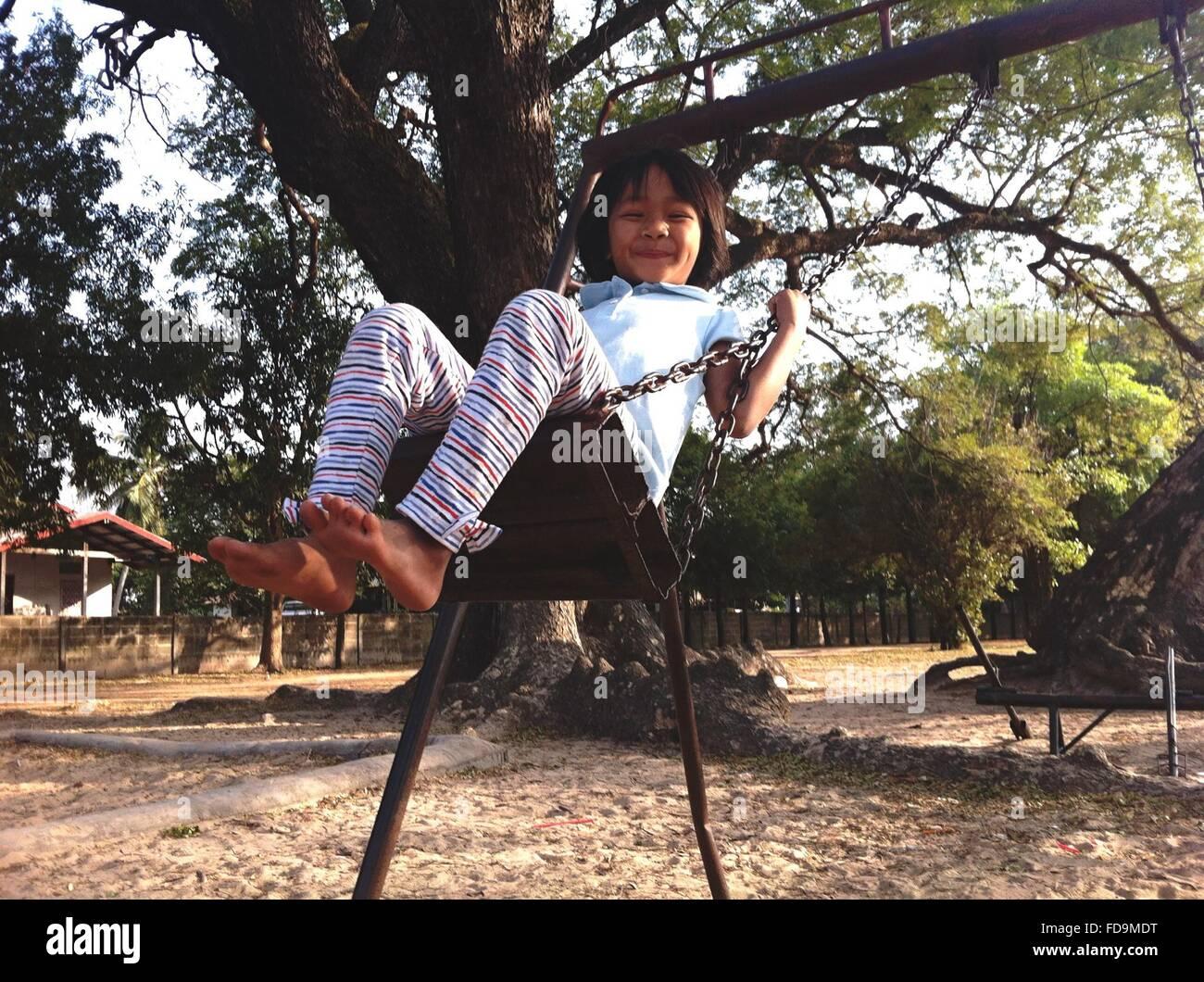 Fille se balançant sur la chaîne en rotation et souriant Banque D'Images