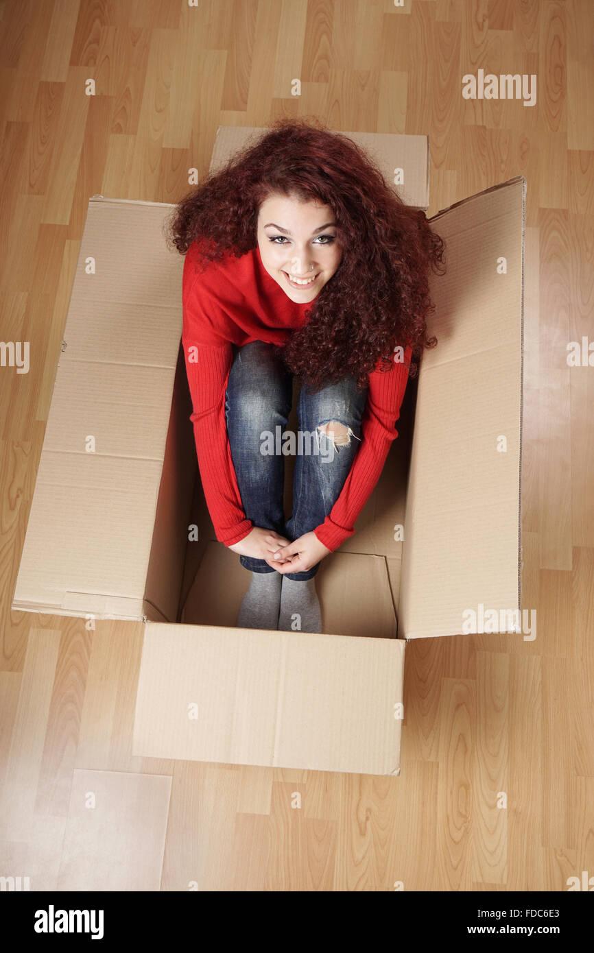 Girl sitting in cardboard box Photo Stock