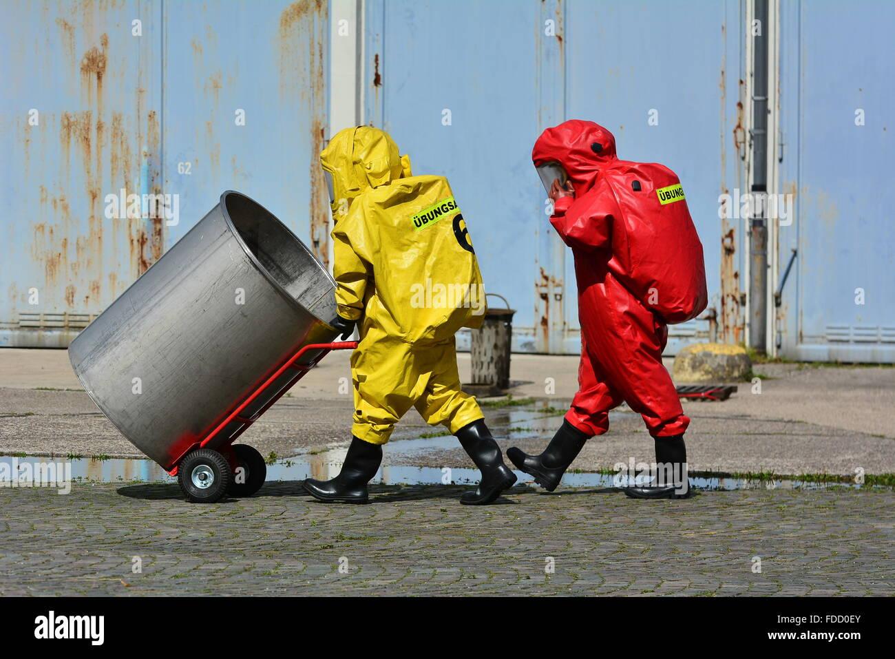 Travailleurs en uniforme de protection masque,transport,gants et bottes de barils de produits chimiques Photo Stock