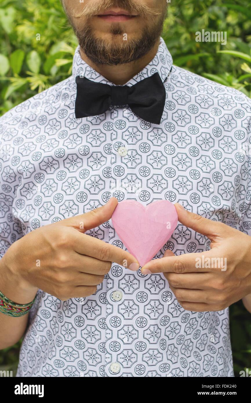 Homme tenant un objet de forme coeur en face de la poitrine Banque D'Images
