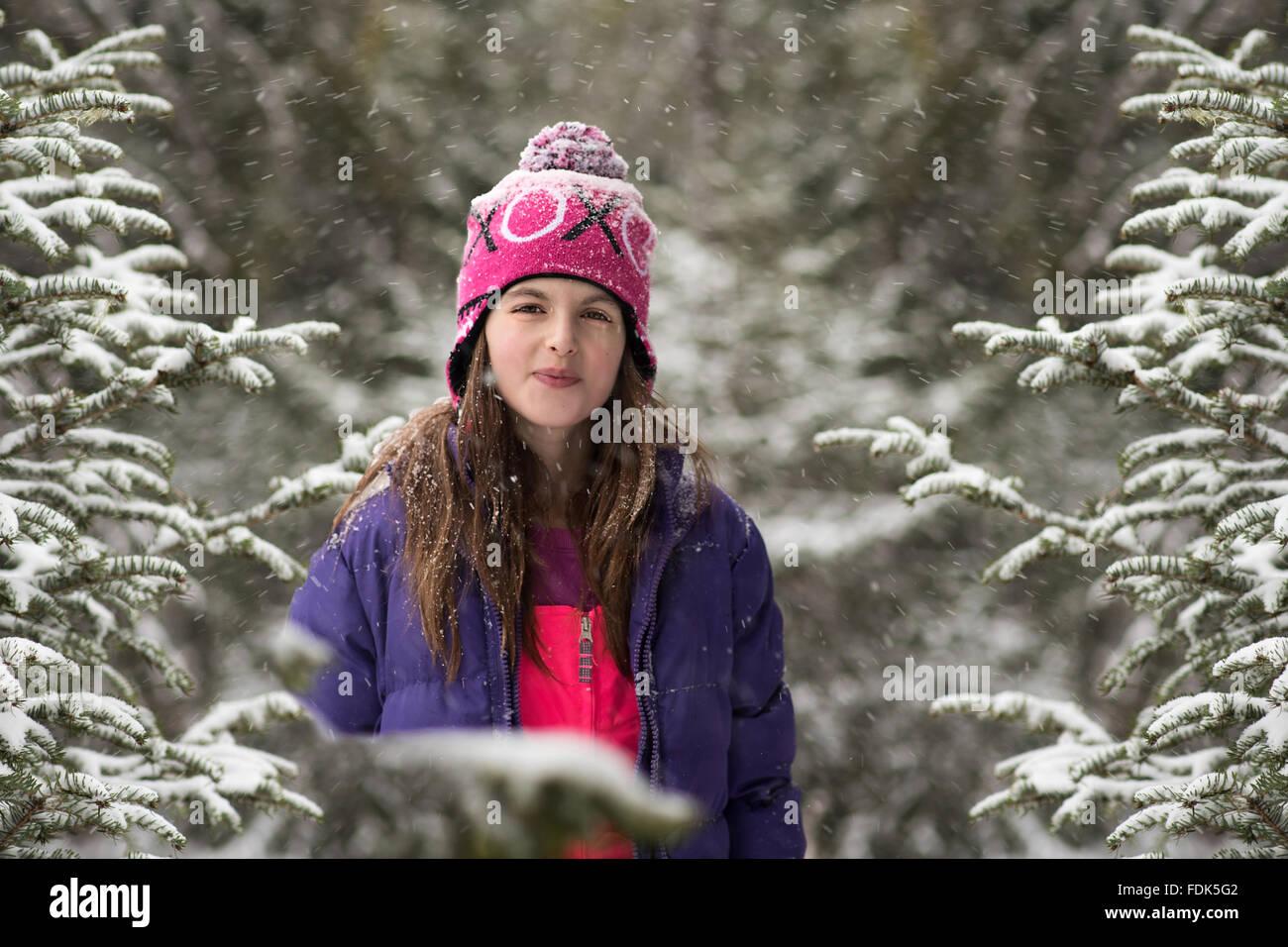 Smiling girl debout dans la forêt dans la neige Banque D'Images