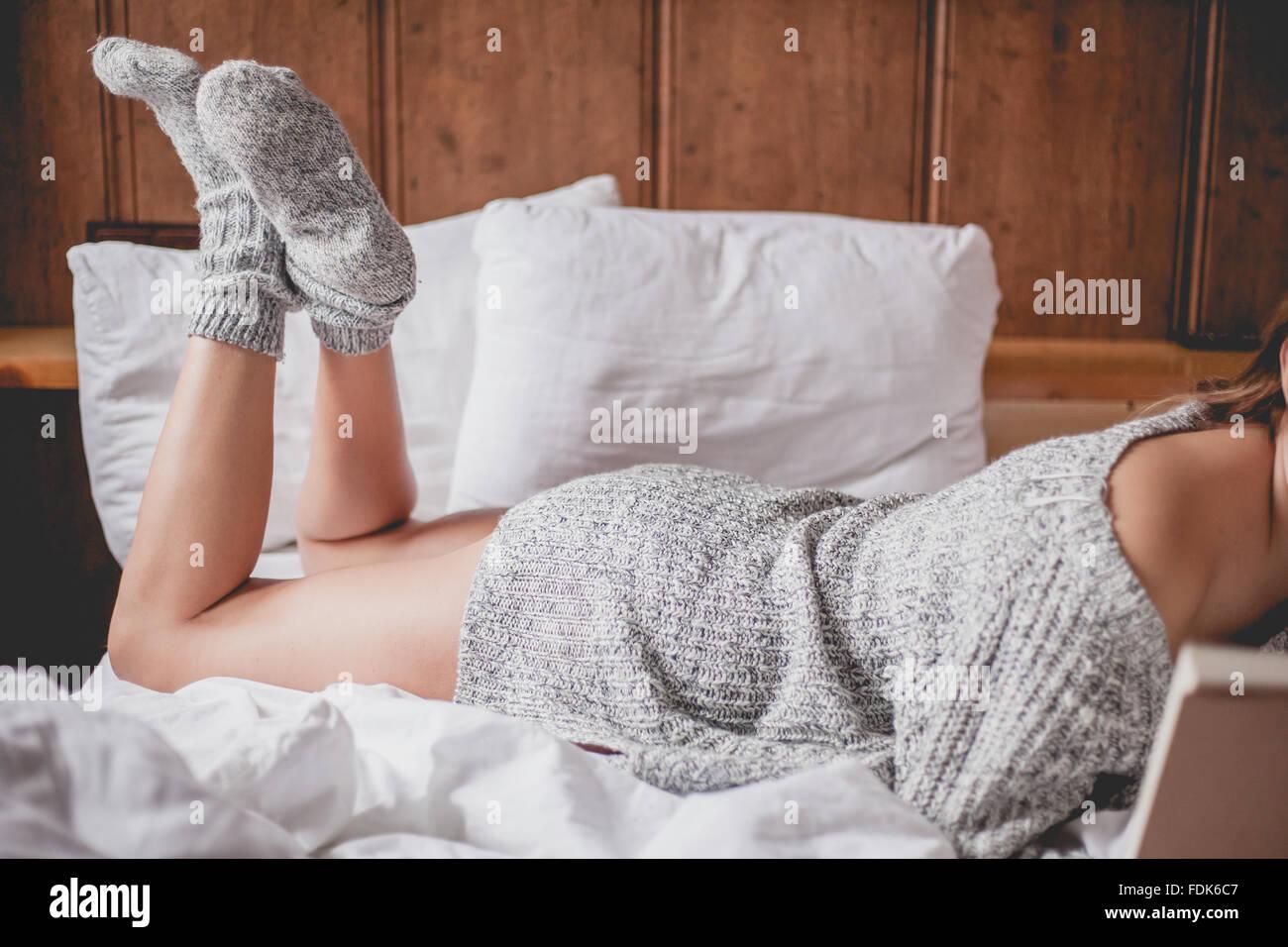 Vue latérale d'une femme allongée sur un lit un livre de lecture Banque D'Images