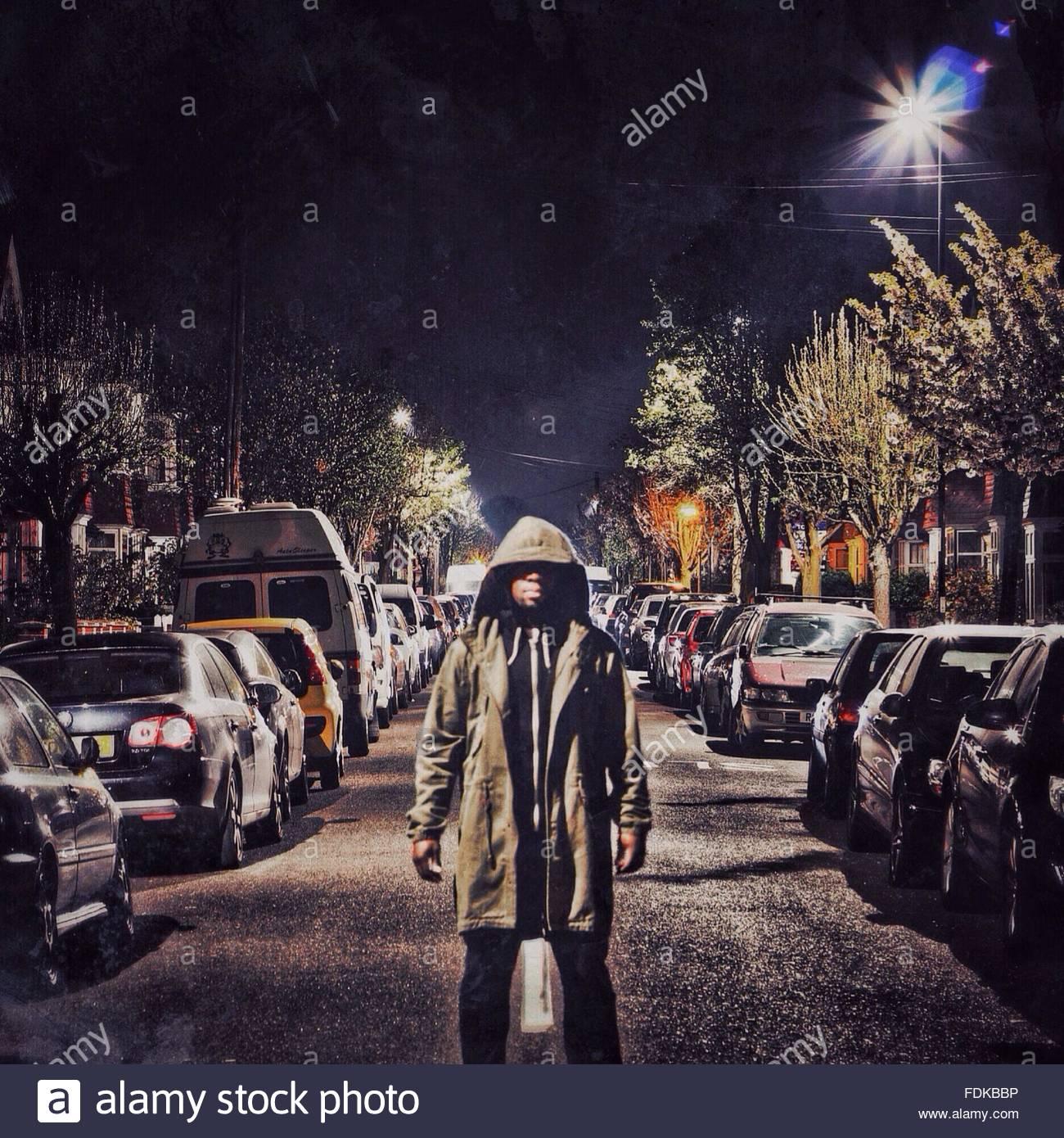 Jeune homme sérieux à Hood Standing Outdoors Photo Stock