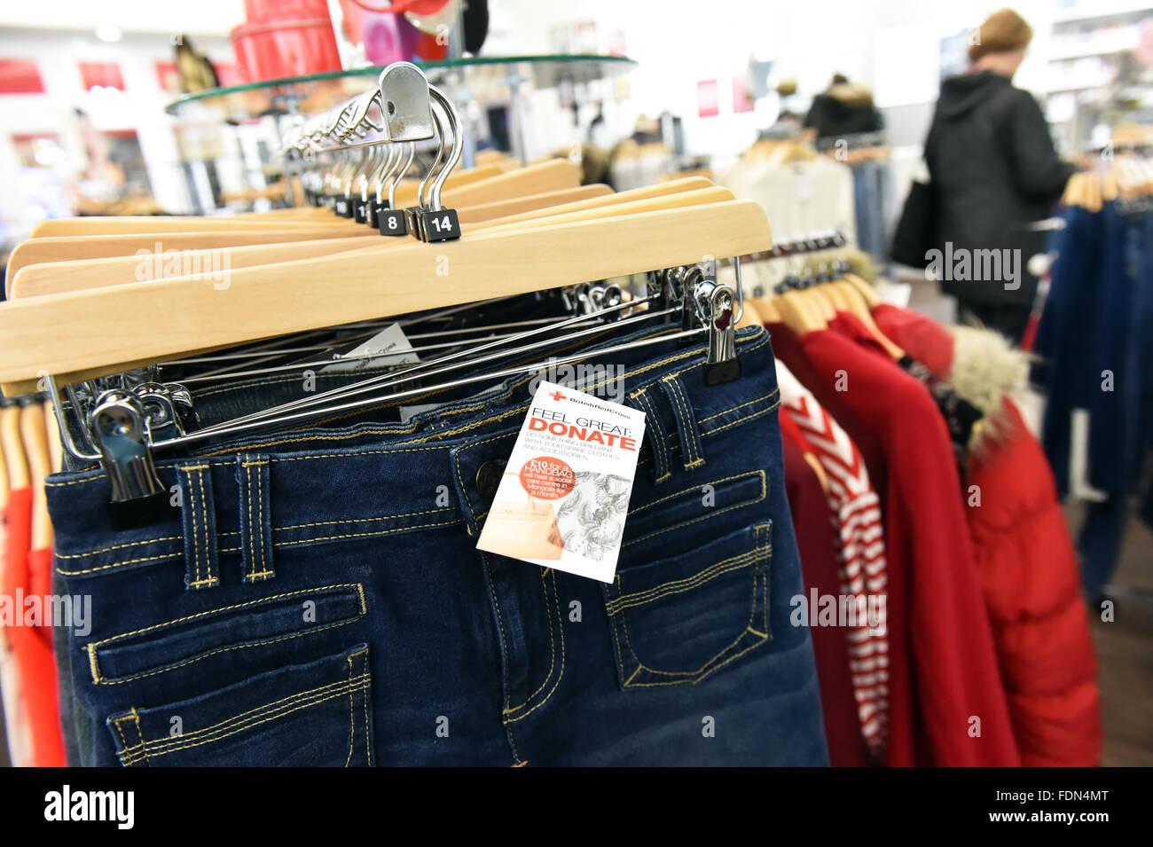 Vêtements affiché dans un magasin de charité UK accroché sur des cintres. Photo Stock