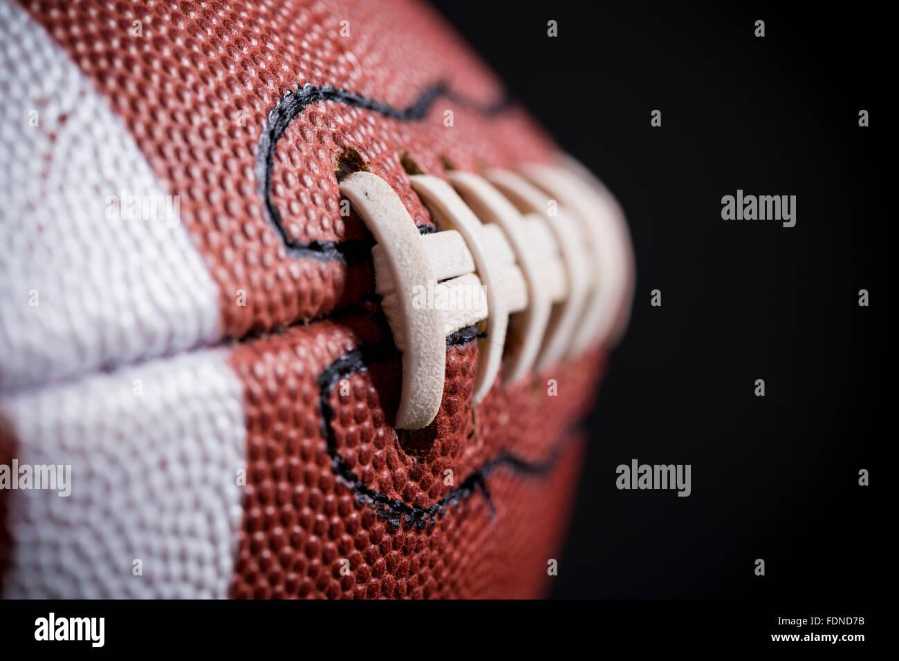 Un football américain en cuir sur fond noir Photo Stock