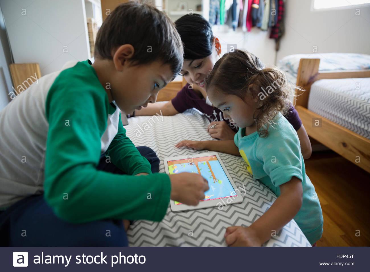 Mère et enfants jouant jeu sur tablette numérique Photo Stock