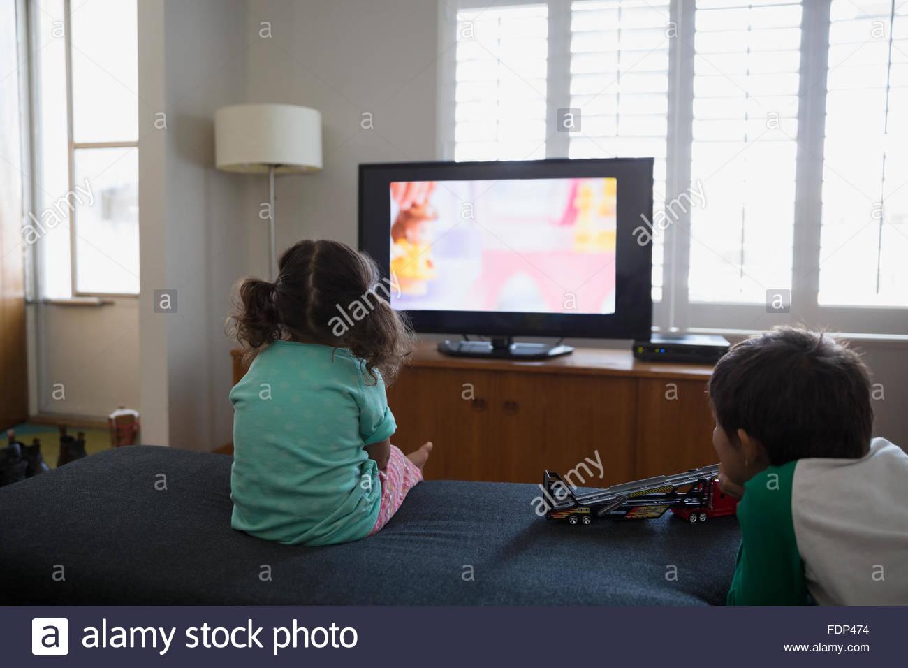 Frère et sœur regarder les dessins animés dans la salle de séjour Photo Stock