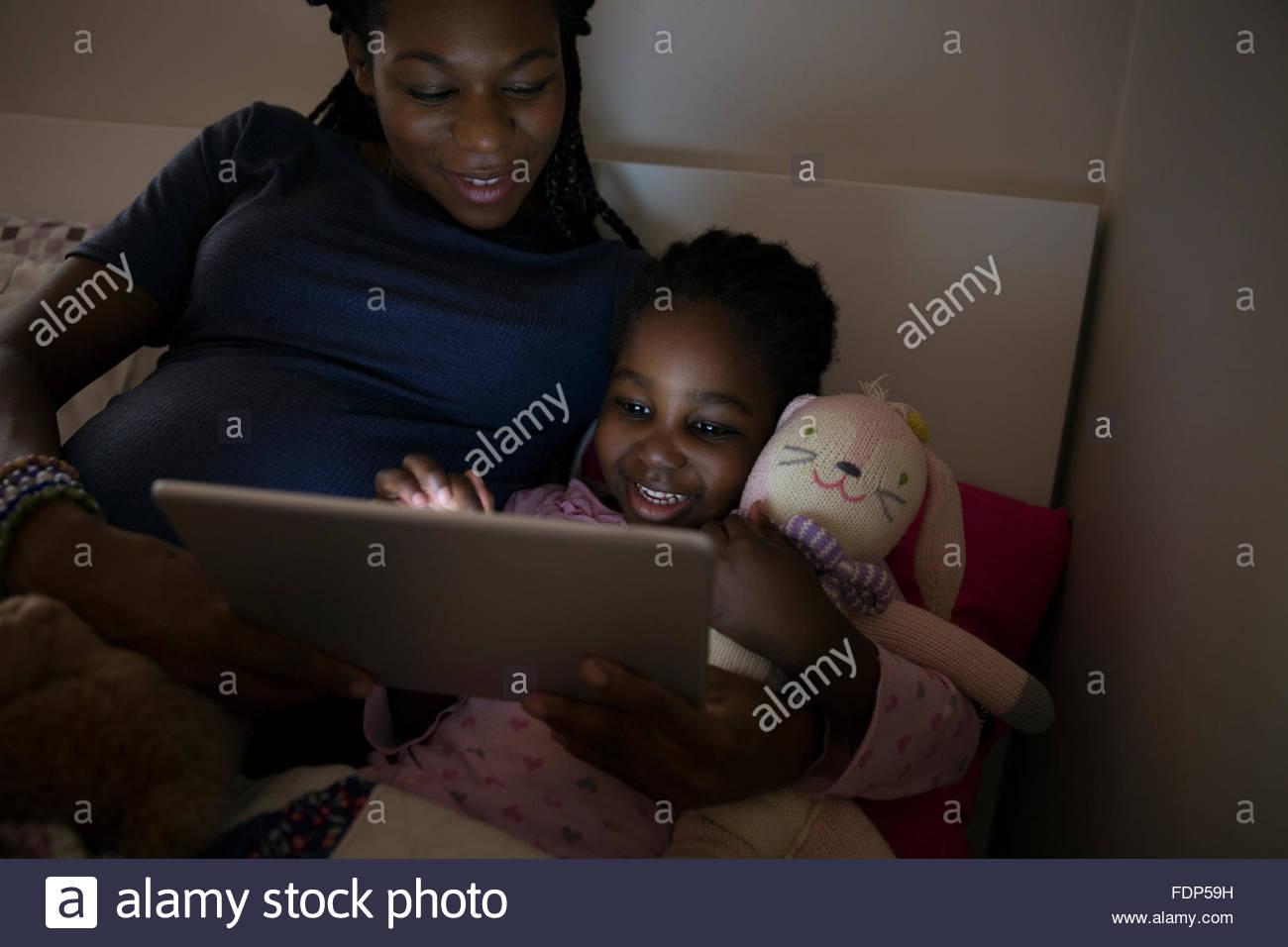 Mère et fille à l'aide de tablette numérique à l'heure du coucher Photo Stock