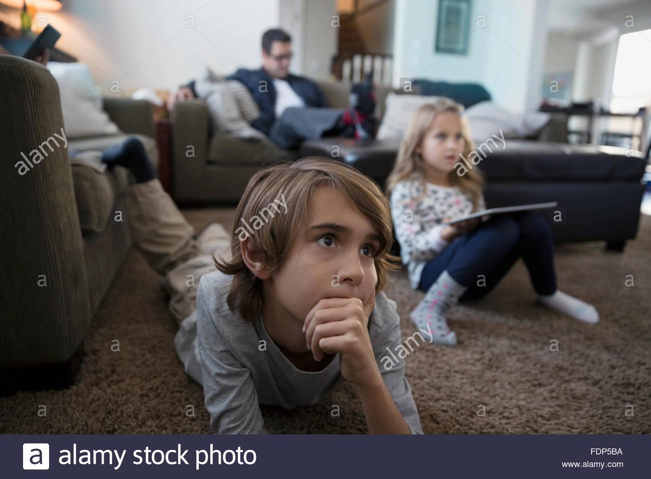 Garçon sérieux regardant la TV sur plancher du salon Photo Stock