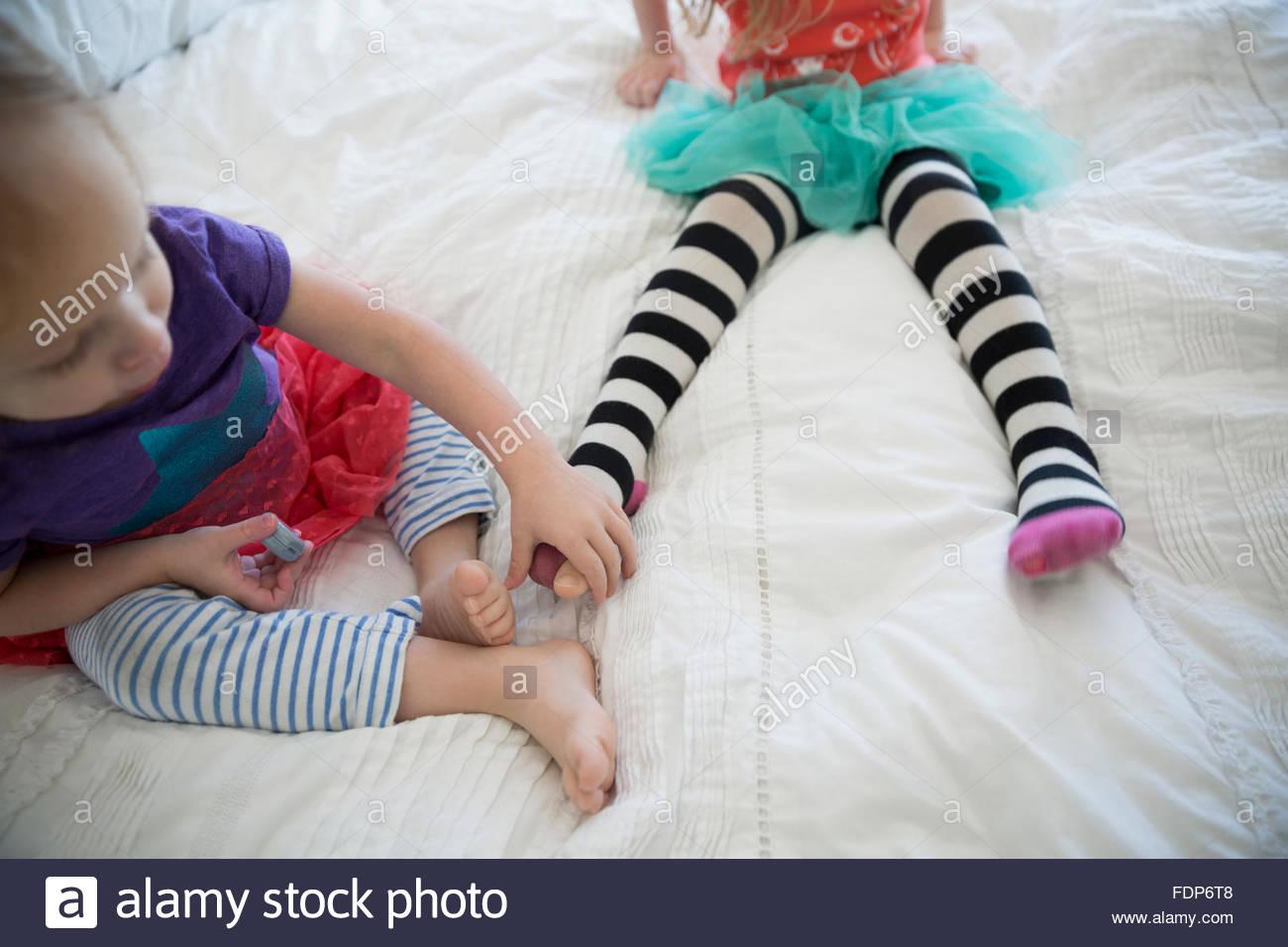Leggings à rayures en sœurs on bed Photo Stock