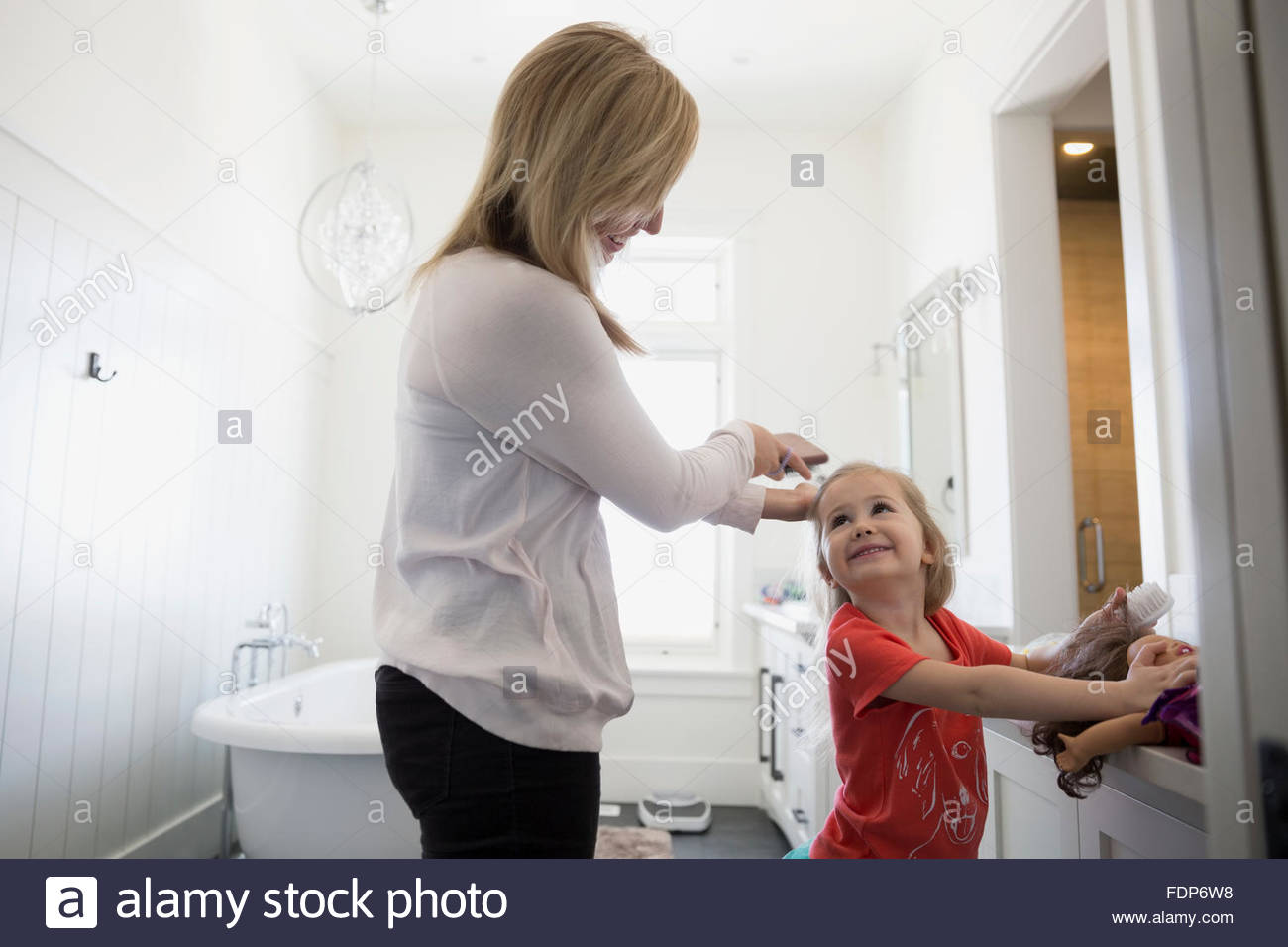 Brossage des cheveux mère filles salle de bains Photo Stock