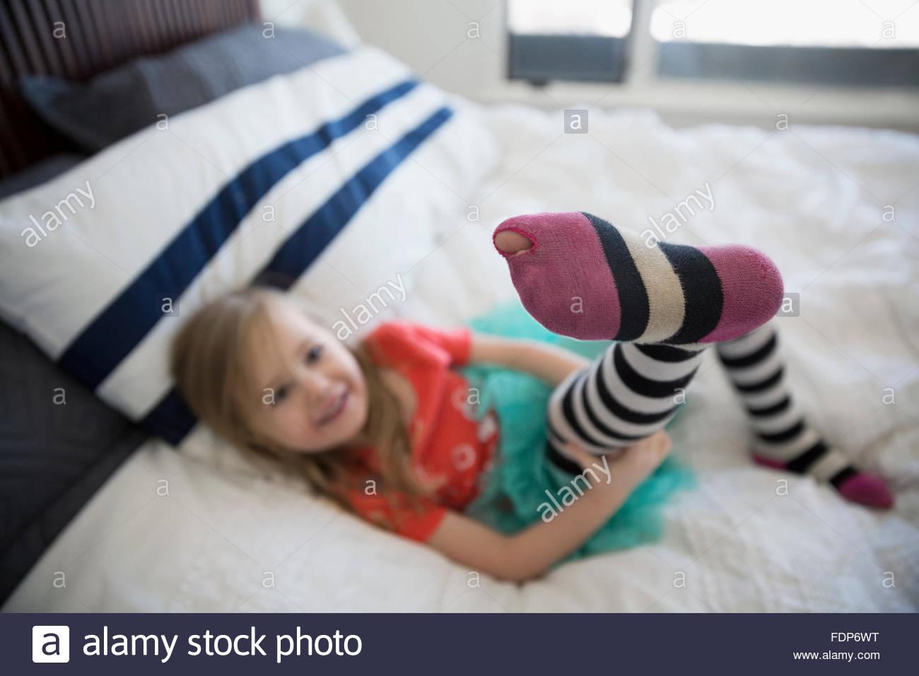 Cute girl montrant toe poussant du trou leggings Photo Stock