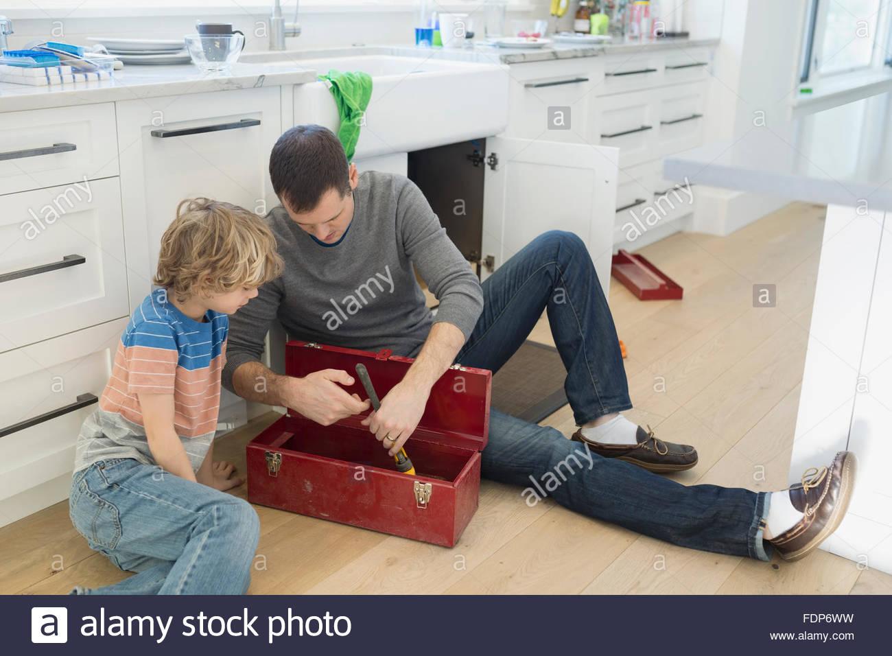 Père et fils l'examen de la boîte à outils l'outil de sol de la cuisine Photo Stock