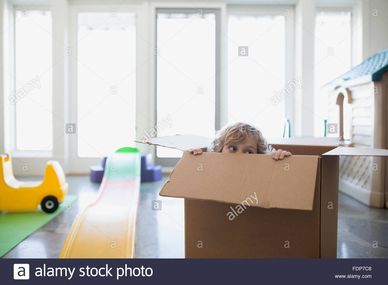 Boy hiding in cardboard box Photo Stock