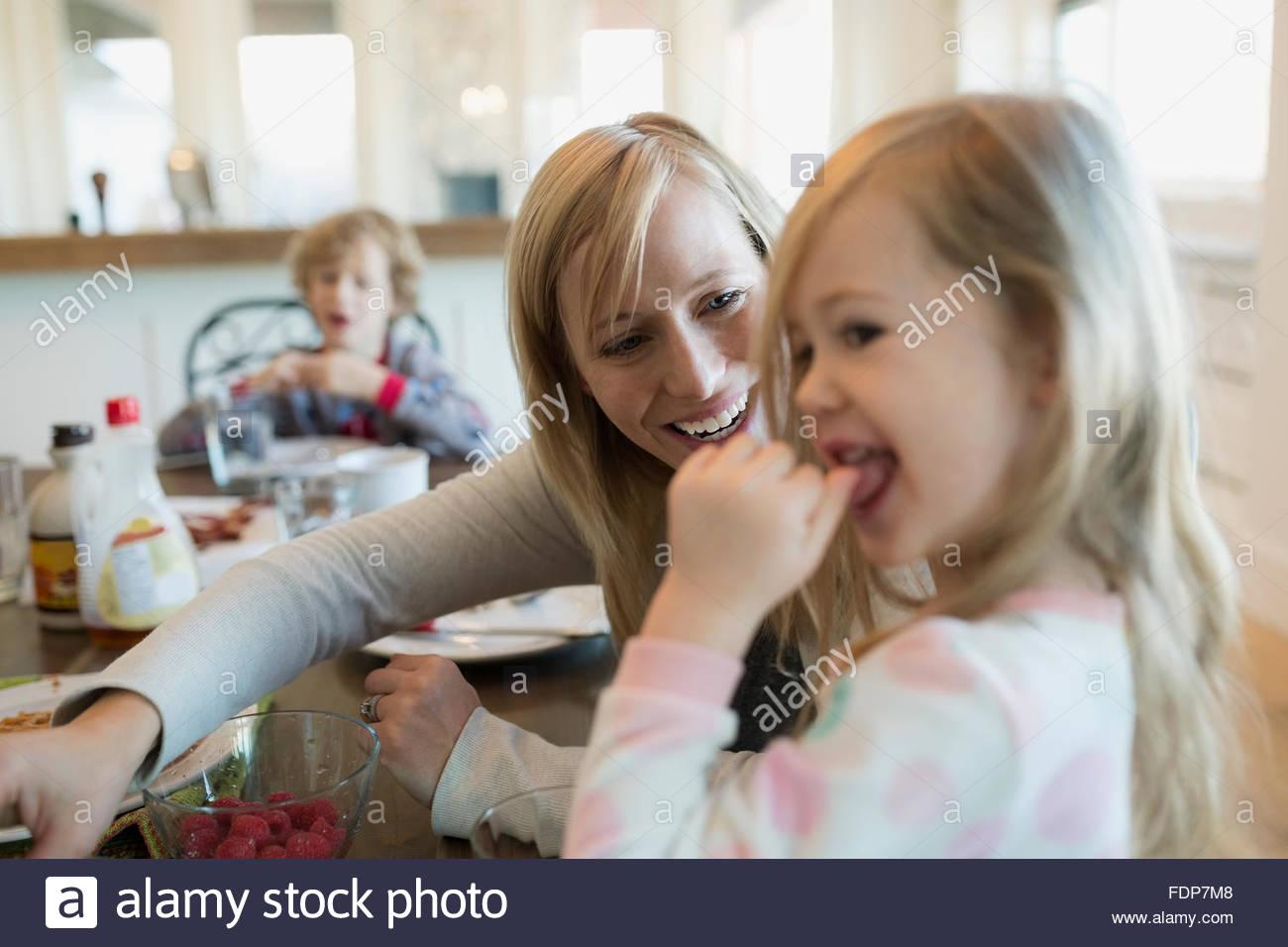Mère et fille de manger des framboises à table de petit déjeuner Photo Stock