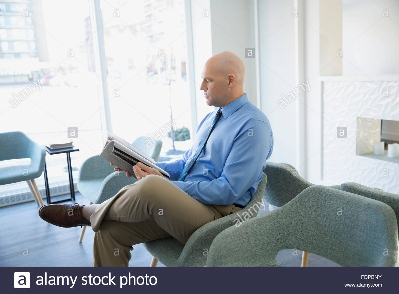 Man reading newspaper en attente dans le hall de la clinique Photo Stock