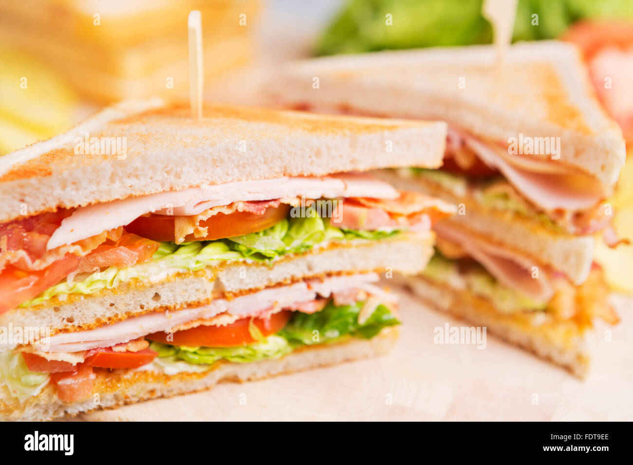 Un club sandwich sur une table rustique dans une lumière vive. Banque D'Images