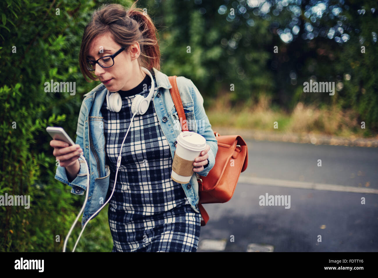 Jeune étudiante à marcher le long en utilisant son téléphone et la tenue d'un café. Photo Stock