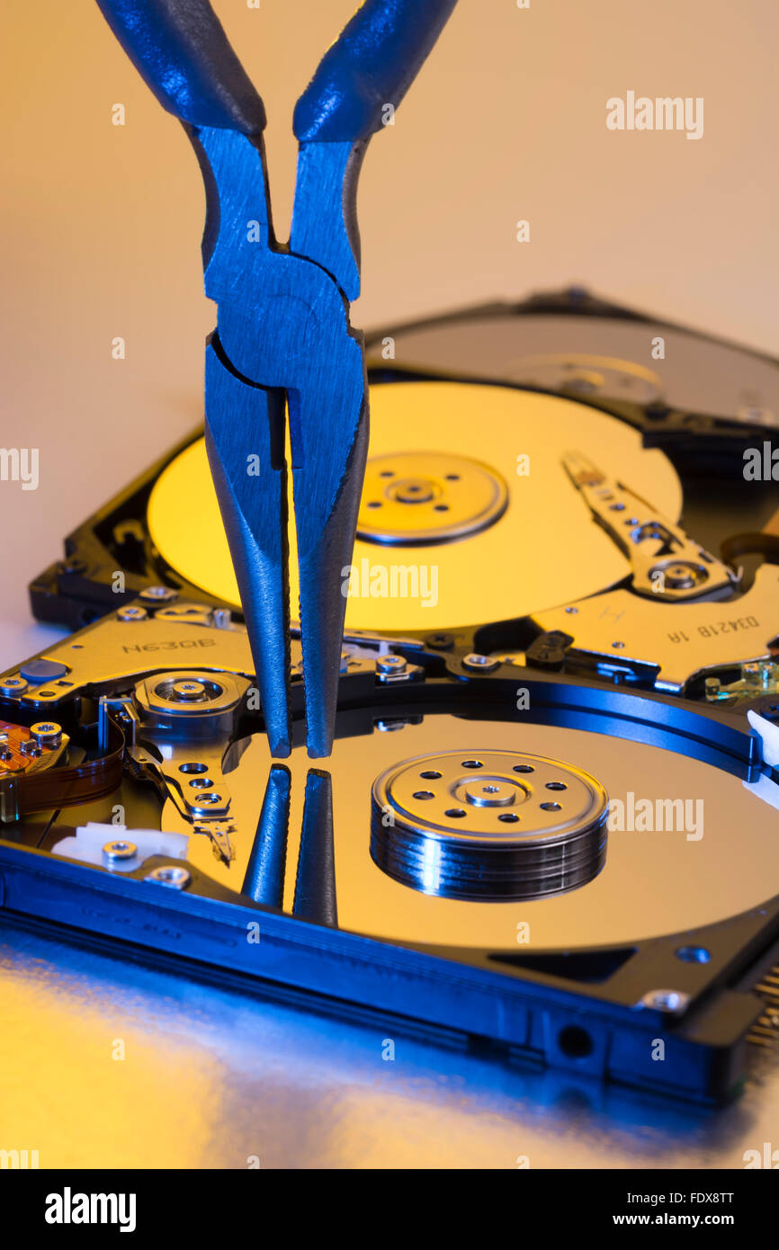 Paire de tenailles bricolage prêts sur un plateau de disque dur dépouillé - métaphore visuelle Photo Stock