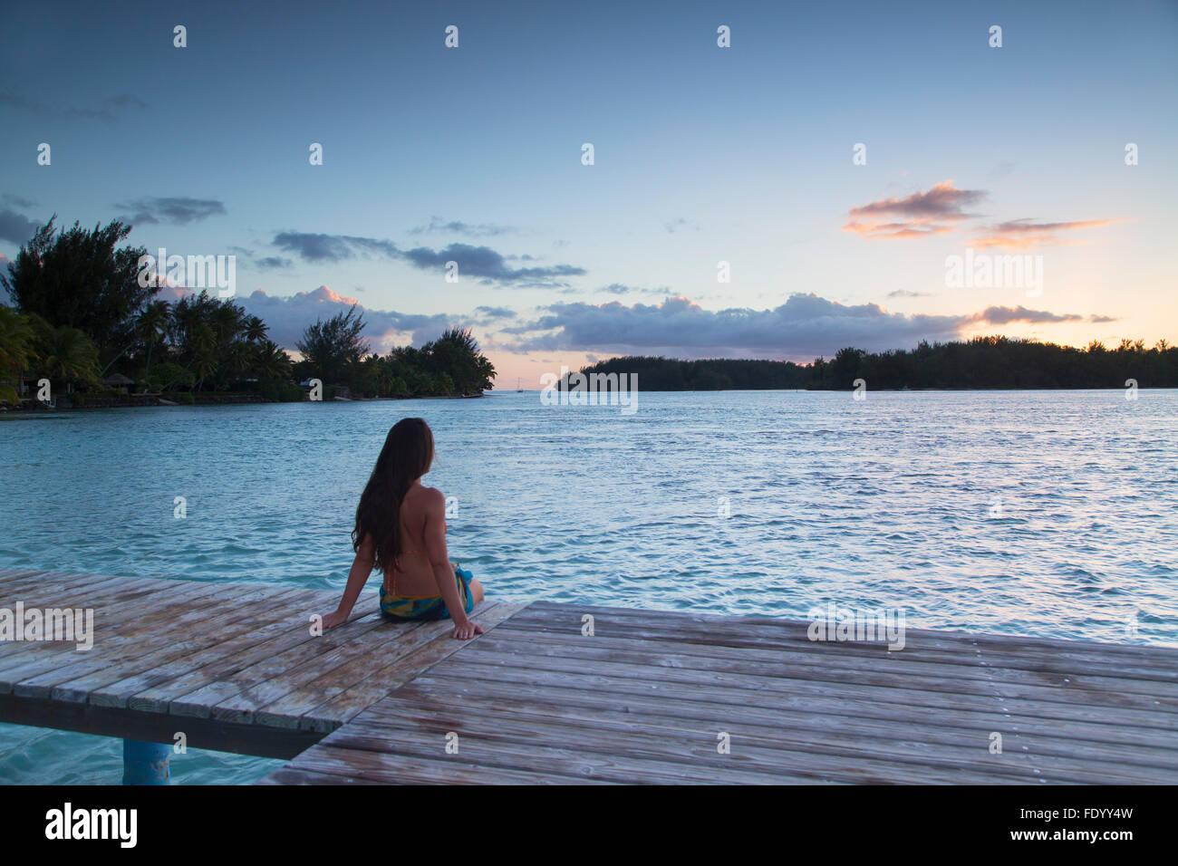 Woman sitting on jetty at sunset, Hauru Point, Mo'orea, îles de la société, Polynésie Française Photo Stock