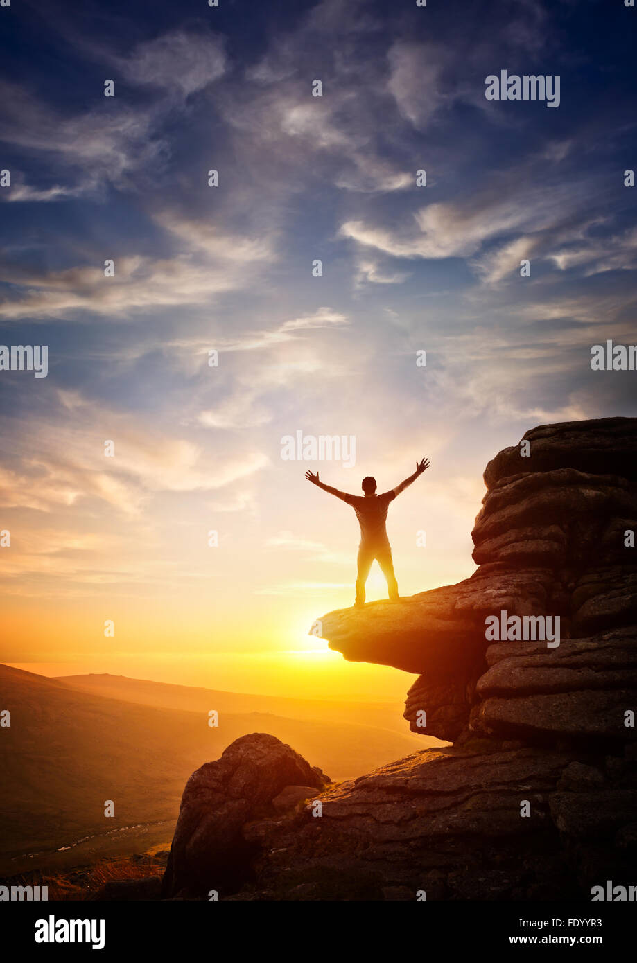 Une personne atteignant jusqu'à partir d'un point élevé, défini dans un coucher du soleil. Photo Stock