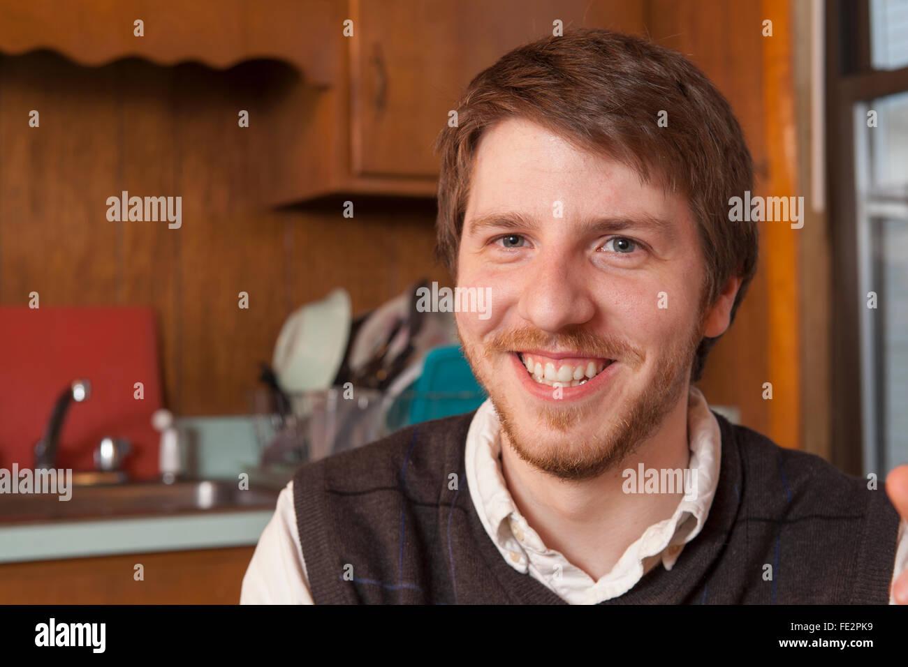 Jeune homme aveugle assis dans sa cuisine et smiling Photo Stock