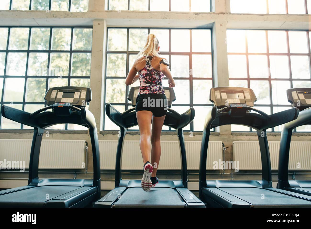De l'horizontale le jogging sur tapis roulant à un club de santé. Femme à une salle de sport Photo Stock