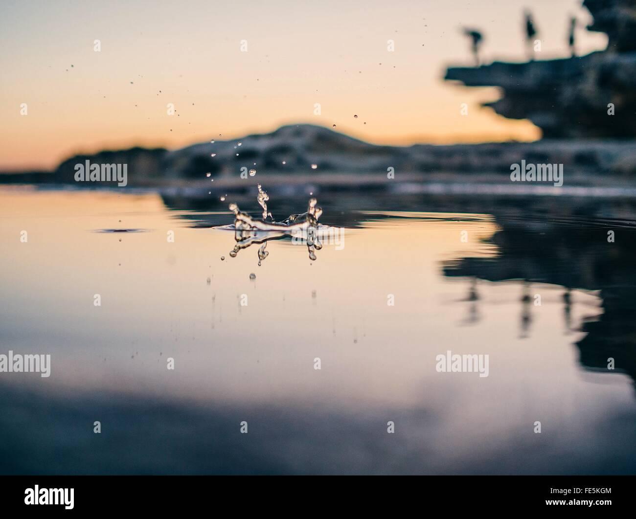 Niveau de la surface de la Goutte tomber dans lac au crépuscule Photo Stock