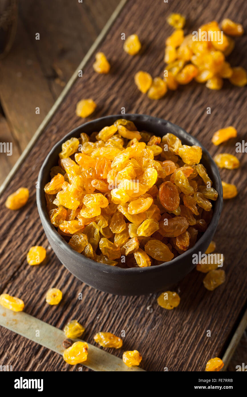 Séché bio Raisins secs dans un bol d'Or Photo Stock