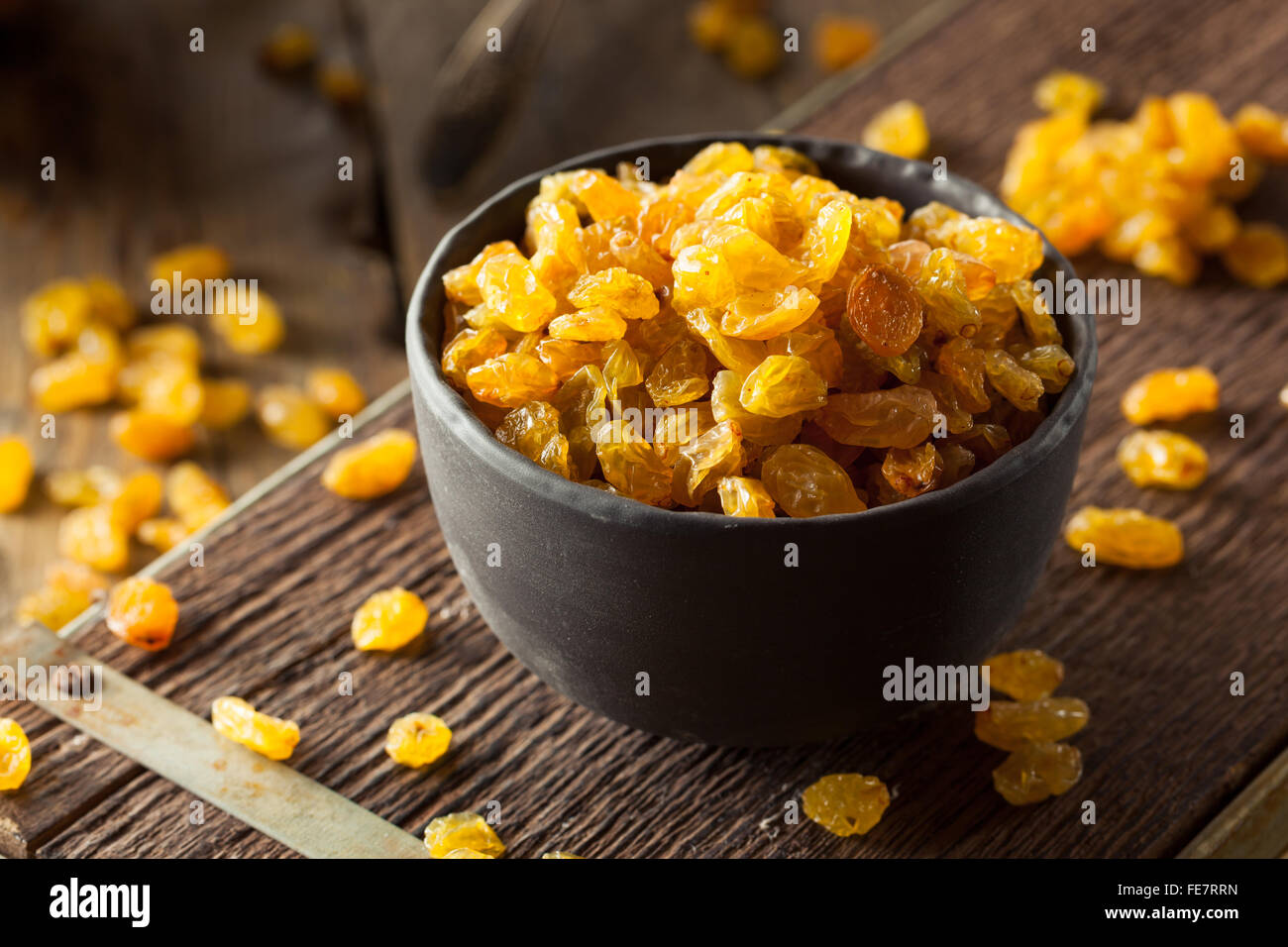 Séché bio Raisins secs dans un bol d'Or Banque D'Images