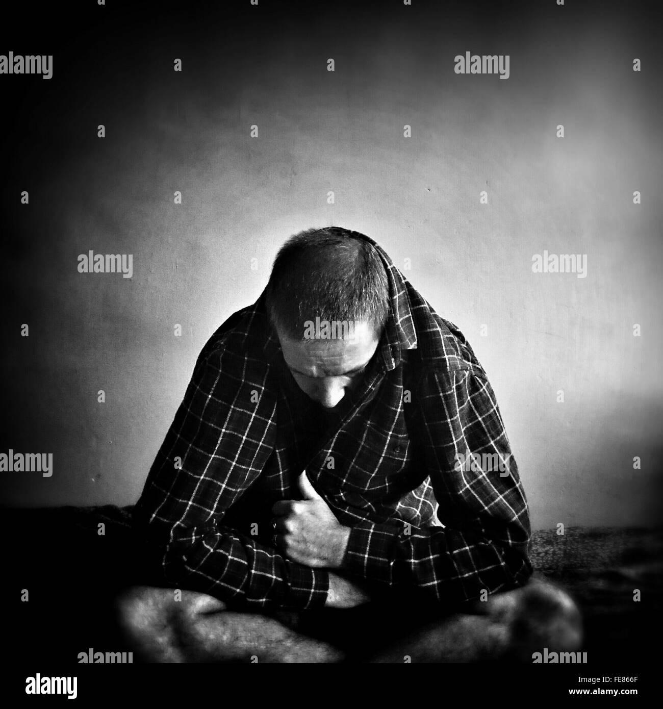 L'homme déprimé assis dans Chambre Photo Stock