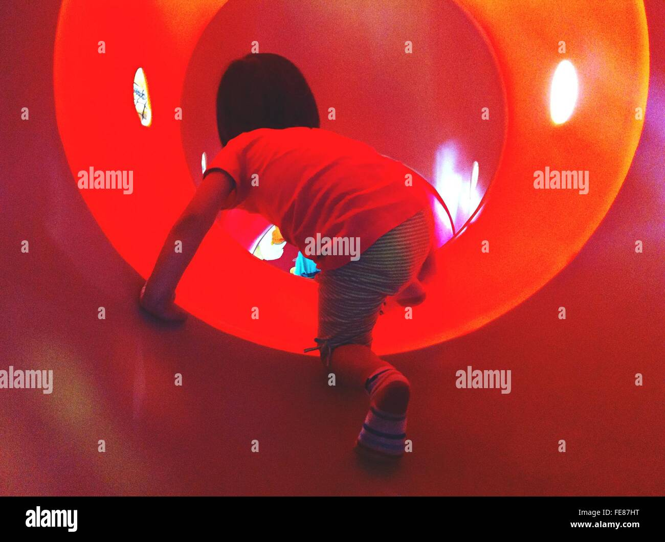 Garçon en tunnel au Jeu pour Enfants Photo Stock