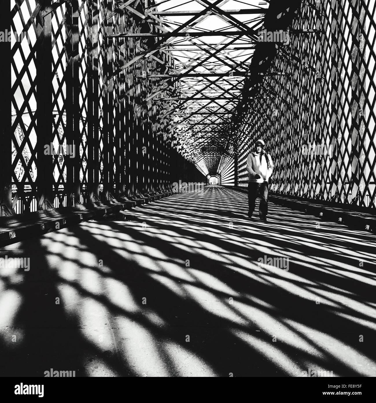 Homme marchant sur le pont Photo Stock