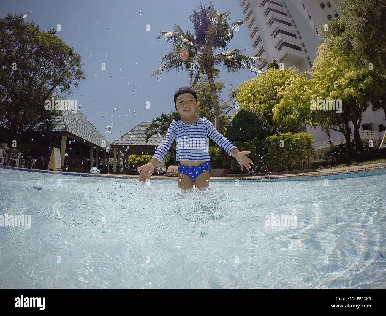 Garçon sautant dans la piscine Banque D'Images