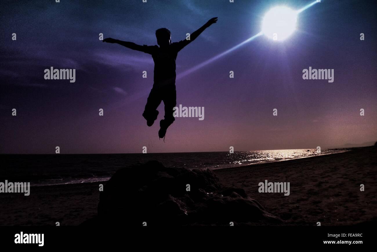 L'homme Silhouette sautant à la lumière du soleil Photo Stock