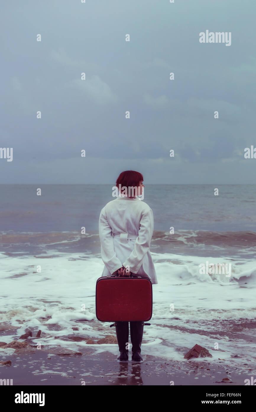Une femme en blouse blanche avec une valise rouge à la mer en hiver Banque D'Images