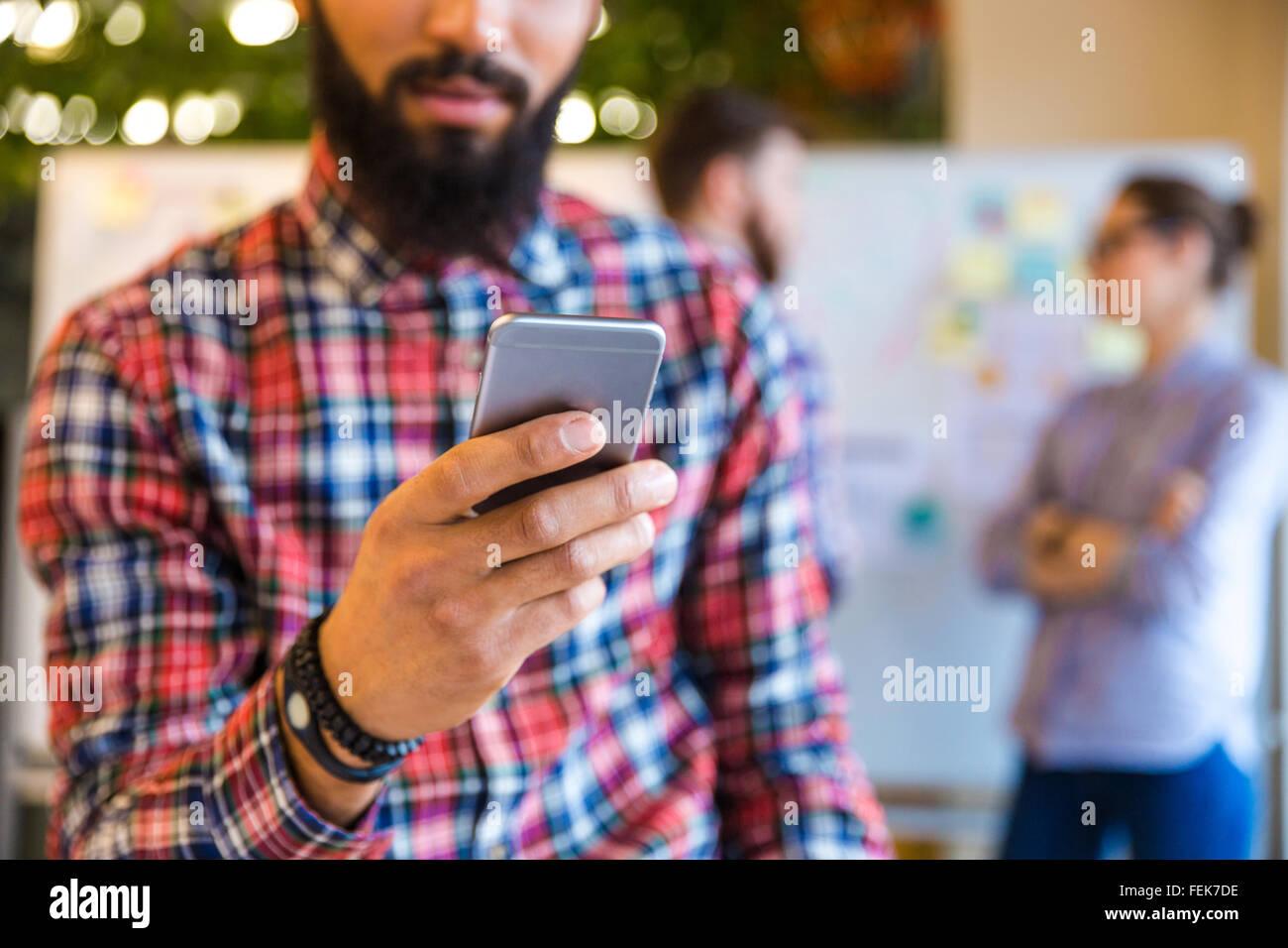 Portrait d'afro-américain man using smartphone in office avec des collègues à l'arrière Photo Stock
