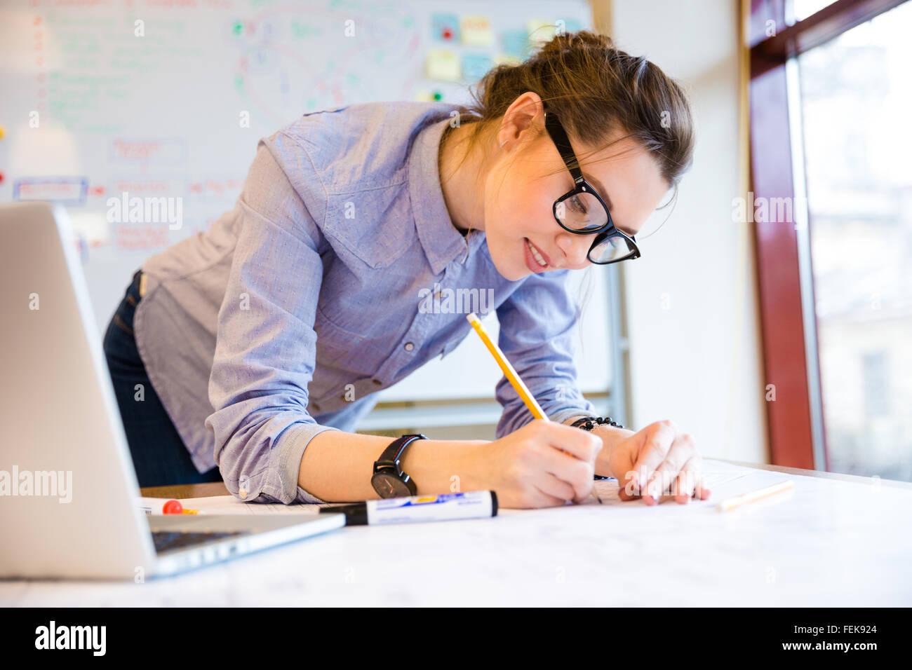 Smiling pretty young woman drawing plan directeur sur la table près de la fenêtre Photo Stock