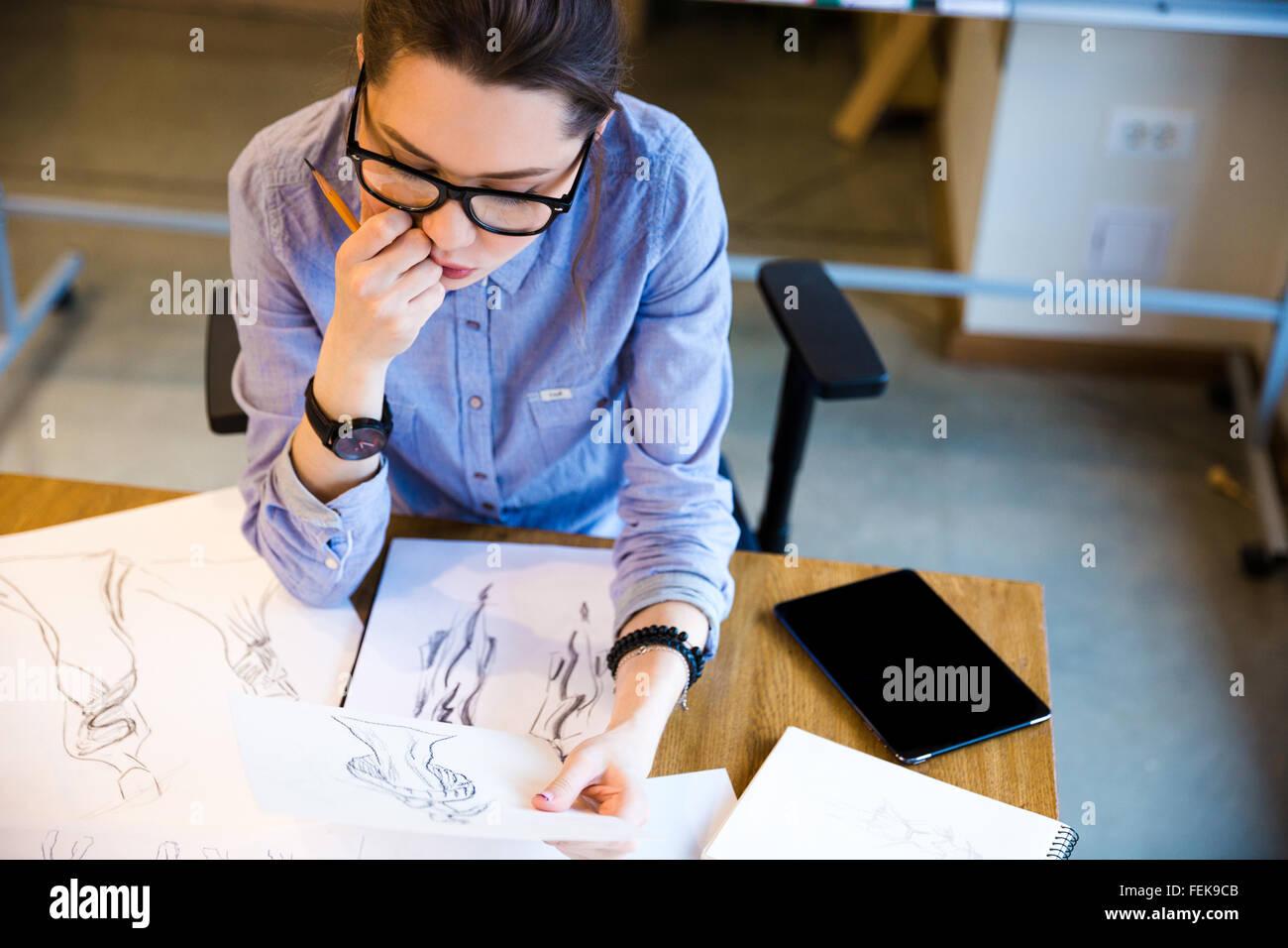 Vue de dessus pensive jolie jeune femme Fashion designer assis sur lieu de travail et à la recherche de croquis Photo Stock