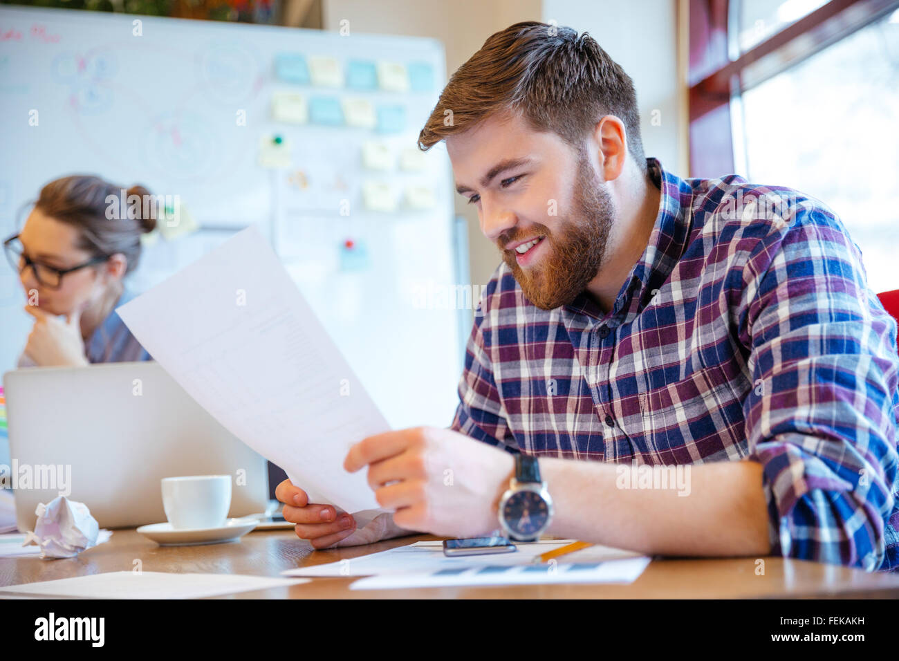 Happy young woman reading paper in office Photo Stock