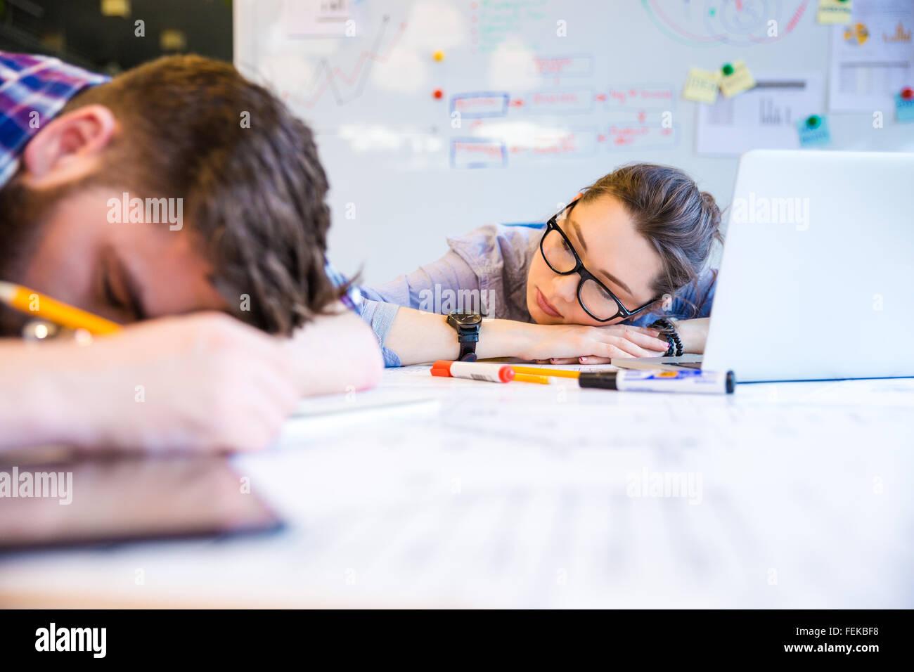 Épuisé jeune femme et l'homme dort sur la table in office Photo Stock