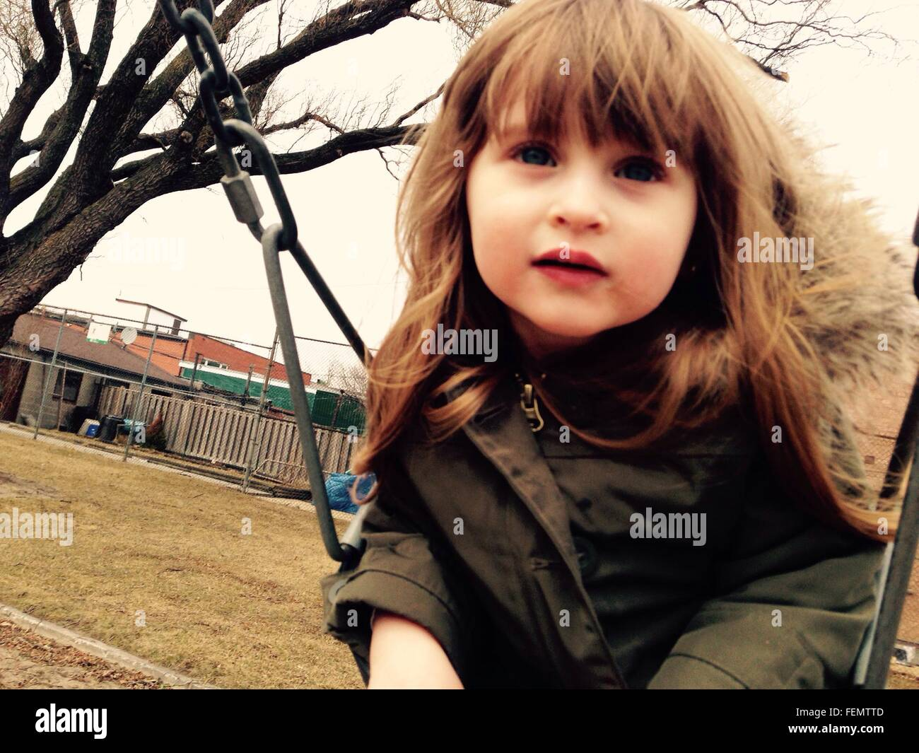 Portrait of Girl Sitting on Chain Swing Ride Photo Stock