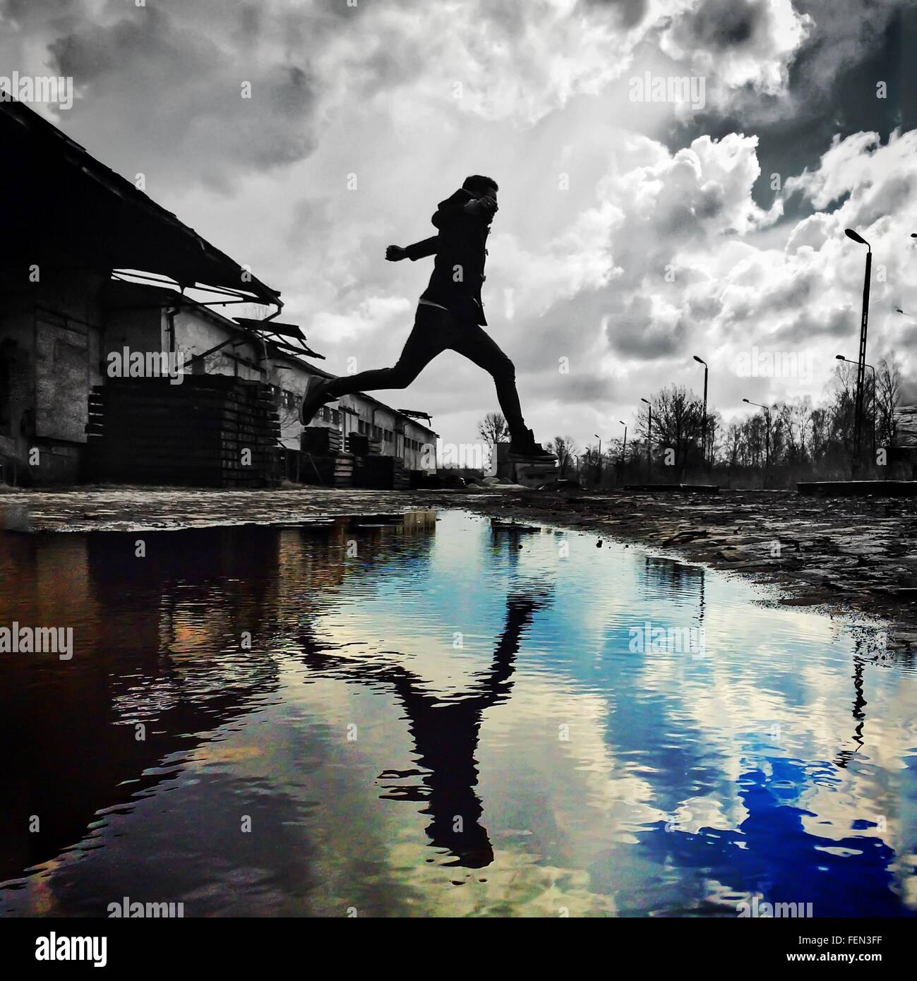 Man Jumping Over Stream Photo Stock