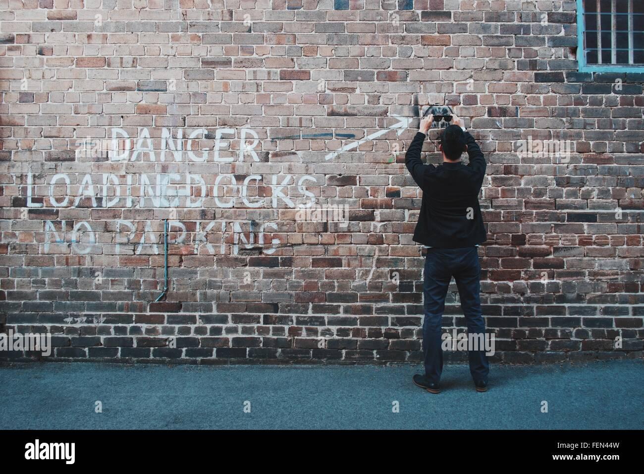 Man Holding Sunglasses en face de mur de brique Photo Stock