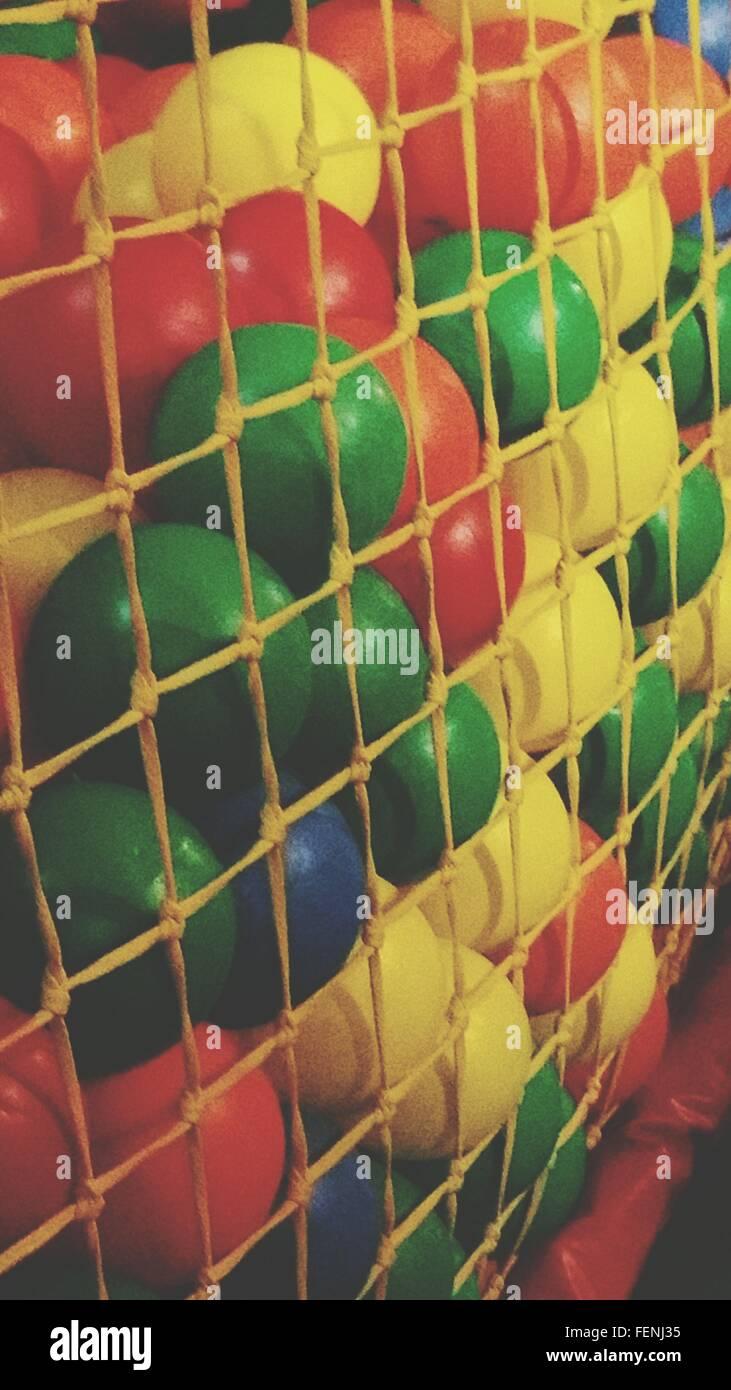 Beaucoup de billes en plastique derrière filets de corde Banque D'Images