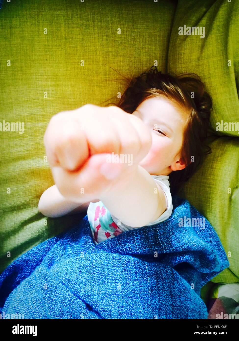 Portrait de jeune fille montrant le poing tout en vous relaxant sur le lit Photo Stock