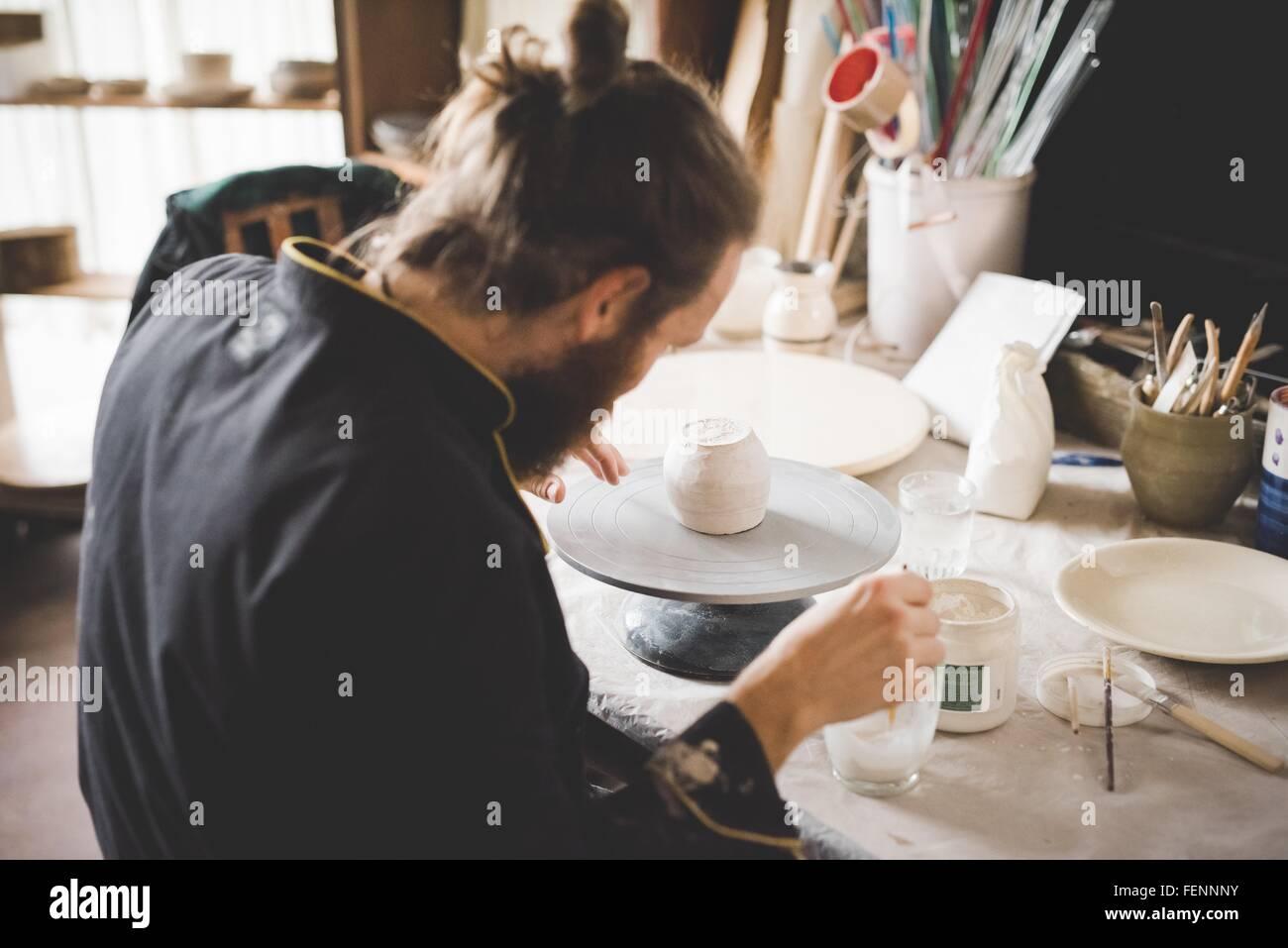 Vue arrière de l'atelier de l'application de la glaçure pour céramique à clay pot Photo Stock